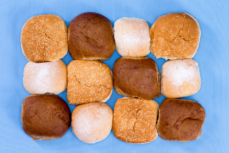 View from above of a variety of freshly baked hamburger buns arranged in three rows isolated on blue photo