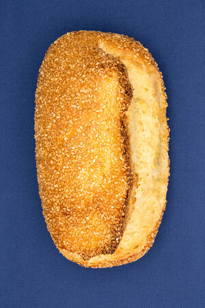 Close up overhead view of a freshly baked crusty golden sesame seed bread loaf showing the texture of the crust and roasted seeds on a blue background photo