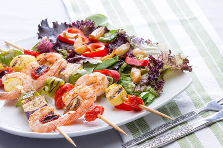 prawn skewers: Serving on a plate of three gourmet shrimp skewers or kebabs with salad greens, tomato and sweet pepper Stock Photo