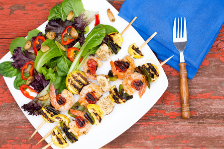 salad greens: Three gourmet shrimp skewers or kebabs with green salad, tomato and sweet pepper, low angle close up on a dinner table Stock Photo