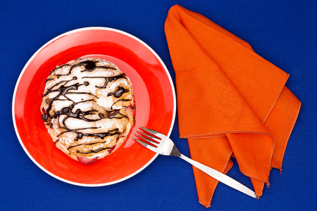 Choux pastry with drizzled chocolate served with orange table setup on blue table cloth photo