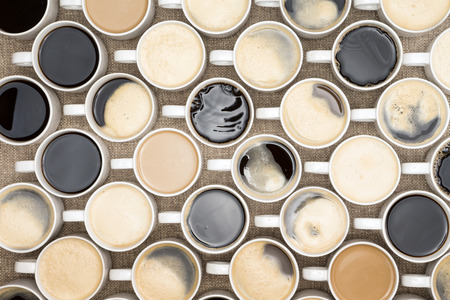 overhead view: Conceptual image of regimented rows of coffee mugs lined up in straight rows with their handles facing the same direction
