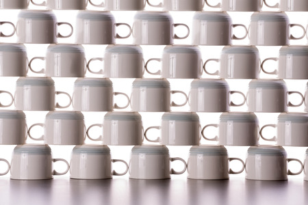 neatly stacked: Abstract background pattern of drying coffee cups neatly stacked in rows on top of one another with the handles in each alternating row facing the opposite direction
