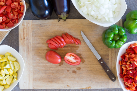 cooking implement: Prepping fresh vegetables for cooking in the kitchen with diced zucchini, tomato, white onion , green capsicum or bell pepper and eggplant arranged around a wooden chopping board with a knife