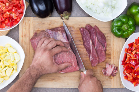 slicing: Hands of a man preparing meat and vegetables in a kitchen slicing lean meat on a wooden board with diced zucchini, tomato and onion and whole eggplant and green bell pepper