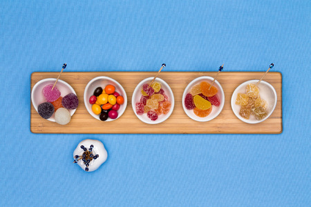 gelatine: Bowls of different gummy candies with crystalised sugar coating, jujubes, jelly beans and fruity gums arranged in a row on a wooden board centered on a blue background with copyspace Stock Photo