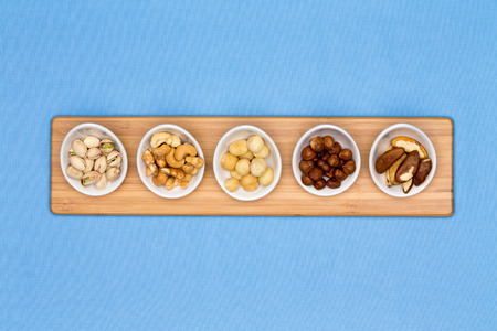 centered: Taster dishes of assorted nuts containing cashews, pistachio, macadamia, hazel and brazil nuts arranged in a row on a wooden board centered on a blue background with copyspace