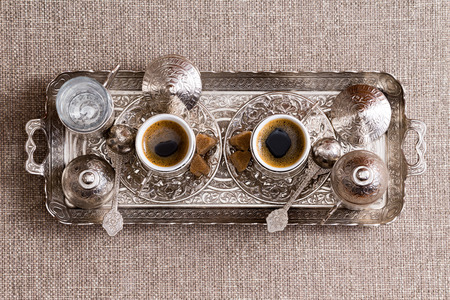 turkish: Traditional ornate metal tray with two matching cups of freshly brewed Turkish coffee with sugar, lids and a pot or cezve viewed from above