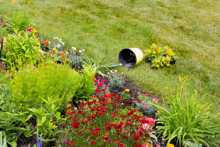 toppled: Toppled bucket in a beautiful garden with gardening tools inside
