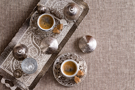 Traditional Turkish coffee for two served on an ornamental copper tray with matching cups, saucers and lids and brown sugar on a textured neutral table cloth