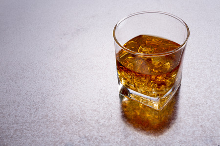 High angle view of a glass of whiskey on a shiny textured metal bar counter with copyspace to the left and a reflection photo