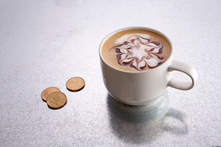 baristas: Baristas appreciate receiving a tip for their service, a conceptual image with a cup of cappuccino coffee with a decorative pattern on a bar counter with loose coins or small change as a gratuity Stock Photo
