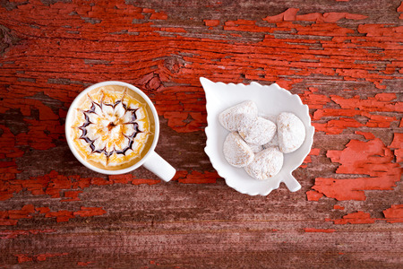 sugarcoated: Mug of delicious caramel chocolate latte with espresso coffee and a decorative pattern on the froth served with a leaf-shaped bowl of sugar coated wedge cookies on a rustic grungy red wooden table Stock Photo