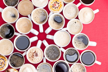 Coffee mecca with multiple assorted types and flavors of coffee in identical white mugs artistically arranged with converging handles in the centre on a red background, overhead view