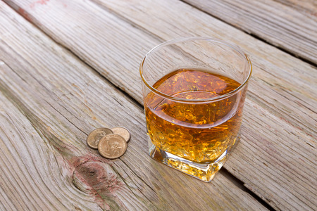 addictive drinking: Tumbler of whiskey and tip of loose coins standing on an old rustic wooden bar counter with diagonal planks and copyspace, high angle view