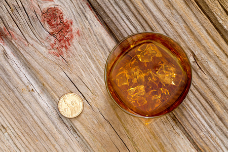 gratuity: Glass of whiskey and a coin for a gratuity or tip standing on an old textured wooden bar counter, view from above with copyspace