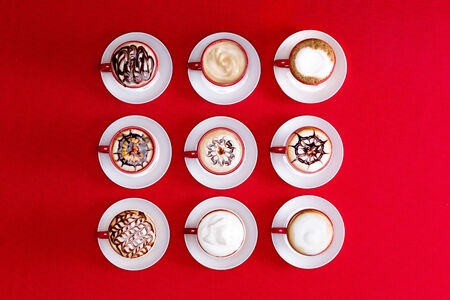 Overhead view of striking patterns and latte art depicted in the foam on espresso or cappuccino coffee in red and white cups and saucers on a red background photo