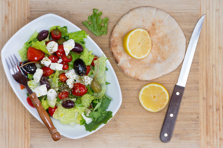 feta cheese: Freshly prepared Mediterranean salad with mixed olives, lettuce, tomato and feta cheese served with lemon for seasoning and freshly baked pita bread on a beige cloth with utensils, overhead view