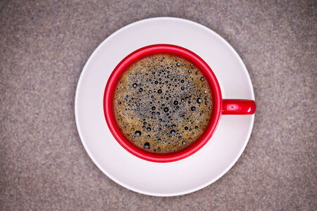 addictive drinking: Freshly brewed frothy black espresso coffee in a red mug on a white saucer centered on a grey cloth with corner vignette, view from above Stock Photo