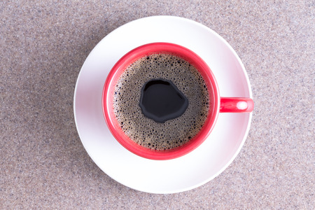 centered: Cup of fresh energising black coffee poured into a red cup on a white saucer centered over a grey cloth background