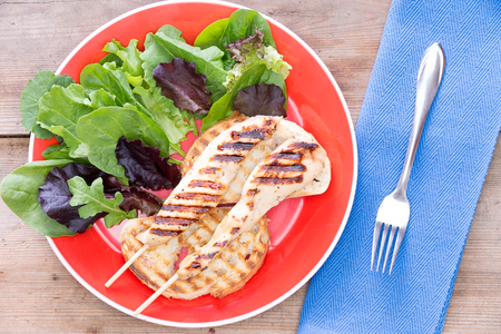 sumptuous: Grilled meat served with leaf vegetables served on a red plate Stock Photo
