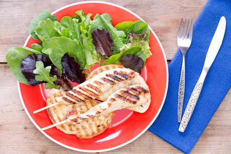 sumptuous: Grilled food served with salad on red plate with fork and knife by its side