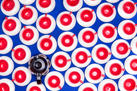 imposition: Overhead background pattern of multiple bright colorful cups and saucers in patriot American red, white and blue with a full coffee pot of espresso coffee in a - coffee on demand - concept