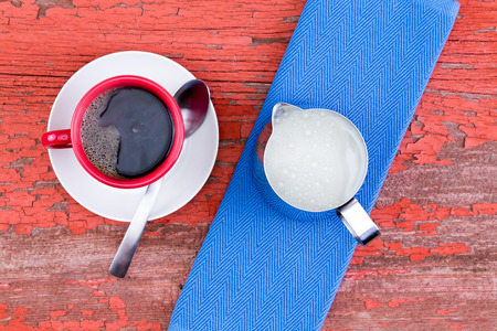 energising: Freshly brewed cup of black coffee in a red mug on a white saucer served with a jug of milk and blue napkin on a grunge wooden rustic red picnic table with flaking paint, view from above