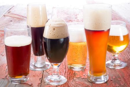 Variedad de cervezas diferentes, de diferentes colores y graduaciones alcohólicas en vasos de diferentes formas, adaptados a diferentes personalidades. Foto de archivo