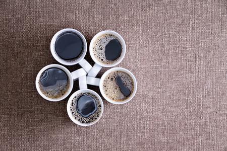 Cinque tazze di porcellana bianca piena di caffè caldo nero, con le bollicine, disposte a forma di pentagono, su una superficie tessile, pronto per essere servito in una riunione sociale, close-up shot dall'alto Archivio Fotografico - 29496958