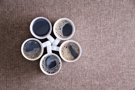 coffee table: Five white porcelain mugs full of fresh hot black coffee, with bubbles, arranged in a pentagon shape, on a textile surface, ready to be served in a social gathering, close-up shot from above