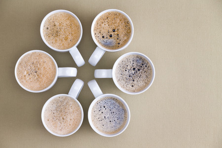 coffee table: Freshly poured coffee topped with frothy bubbles arranged in a circular radiating design with converging handles on a beige background with copyspace, overhead view Stock Photo