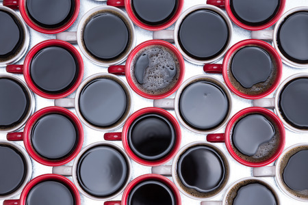energising: Decorative background pattern of black coffee in red and white mugs arranged in alternating rows with all handles facing left on a silver metal surface, overhead closeup view Stock Photo