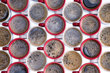 energising: Background pattern of red and white coffee mugs arranged in alternate rows filled with frothy freshly brewed and poured black coffee viewed from above on a metal surface