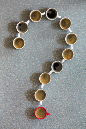 White coffee mugs filled with milky freshly brewed coffee arranged as a question mark with a single red cup as the point on a grey background in a conceptual image, viewed from above