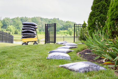 mulch: Mulching the garden takes time and effort with bags of mulch laid out on the lawn alongside the flowerbed in a long row waiting to be spread with a cart stacked full of bags in the background