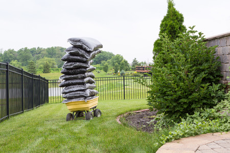 overloaded: Mulch in bags piled high on a cart in the garden teetering precariously as they wait to be spread over the flowerbeds in a carefully manicured rural garden