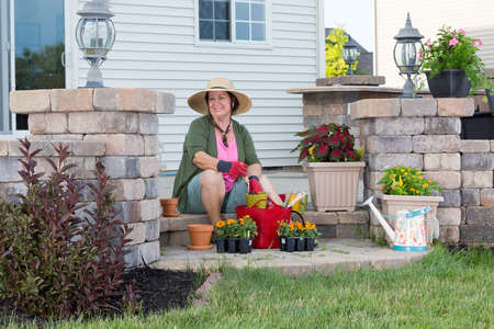 transplanting: Happy stylish elderly Grandma planting in her garden sitting contentedly on the steps of her porch surrounded by plant seedlings in nursery trays transplanting into terracotta flowerpots