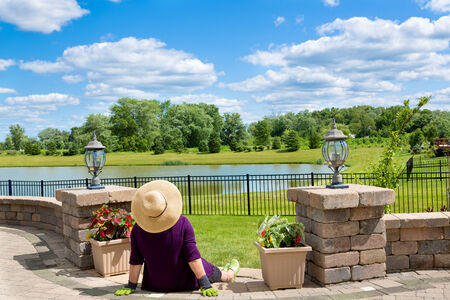 Senior lady gardener taking a break to admire the view from her front patio over a lake and lush green countryside sitting with her back to the camera in a straw sunhat