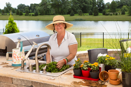 Grandmother in a stylish straw hat standing at the sink on her outdoor patio kitchen caring for her potted plants watering and repotting them into larger containers with a lake backdrop photo