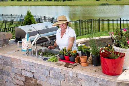 jardineras: Se�ora mayor que trabaja en la cocina de verano en un patio al aire libre de ladrillo cuidar para y encapsulamiento encima de sus plantas de interior en una variedad de macetas y jardineras