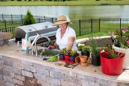 planters: Senior lady working in her summer kitchen on an outdoor brick patio caring for and potting up her houseplants in a variety of flowerpots and planters