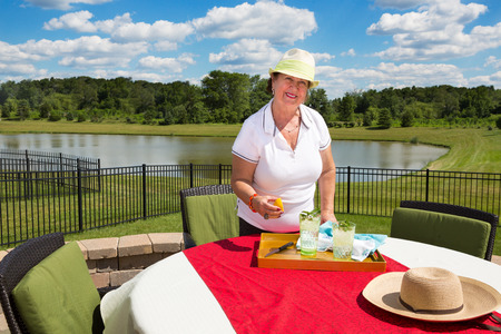 Smiling elderly lady in a trendy sunhat standing at a garden table on an outdoor patio covered in a red cloth preparing glasses of iced water with fresh lemon and mint in scenic countryside photo