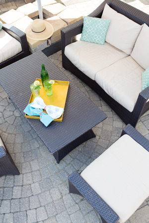 furniture: View from above of a vacant upmarket outdoor patio with modern garden furniture with comfortable upholstered cushions on paving with a central table with a tray of chilled drinks