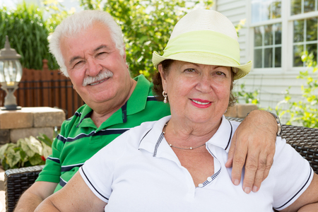 warmly: Attractive healthy happy senior couple sitting arm in arm on an outdoor summer patio in front of their home smiling warmly at the camera