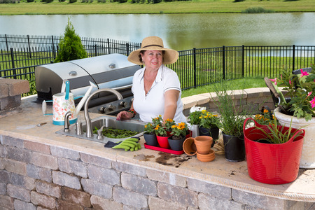 planters: Attractive senior woman caring for her houseplants standing at the sink in her outdoor summer kitchen with a watering can and array of planters and pots smiling up at the camera Stock Photo