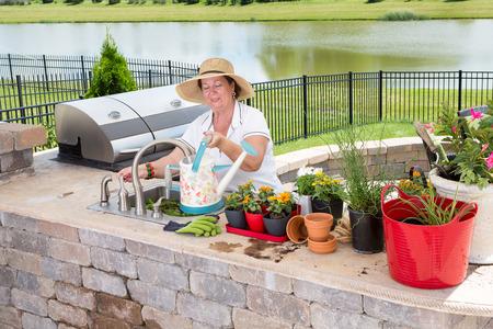 Bejaarde dame neiging om haar potplanten opvullen van een gieter op de wastafel in haar terras keuken als ze zich voorbereidt om ze water, hoge hoek mening met meer achtergrond