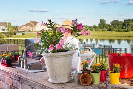 Happy grandmother working in her outdoor kitchen standing at the sink on the open-air patio in her sunhat surrounded by ornamental potted plants peeking through a gap at the camera with a lovely smile photo