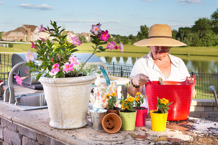 transplants: Elderly lady in a wide-brimmed straw sunhat tending to her potted plants on an outdoor patio overlooking a lake as she transplants and waters them in evening light with a delicate sunset