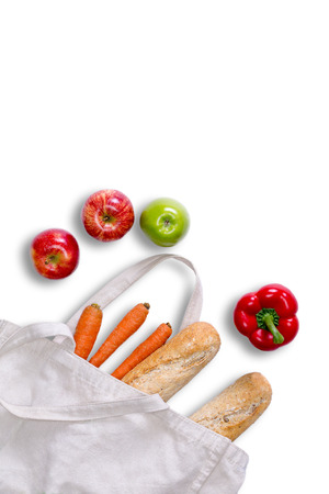tote: Just returned from grocery shopping concept with a white tote bag lying on its side with fresh baguettes, carrots, red bell peppers and red and green apples spilling onto a white surface, view from above